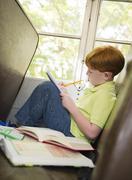 Valkoihoinen poika tekee läksyjä koulubussi Kuvituskuvat