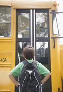 Valkoihoinen poika odottaa koulubussi Kuvituskuvat