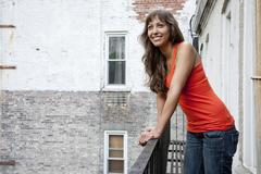 Mixed race woman leaning on fire escape railing Stock Photos