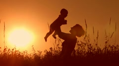 Silhouettes mother and baby sunset Stock Footage