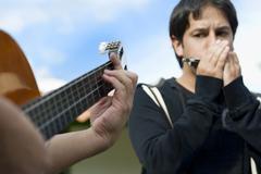 Latinalaisamerikkalainen ystäviä kitaransoiton ja huuliharppu Kuvituskuvat