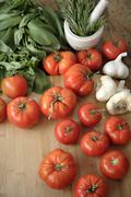 Tomatoes, garlic and basil on cutting board Stock Photos