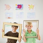 Boys looking through empty frames Stock Photos
