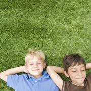 Boys with eyes closed laying in grass Stock Photos