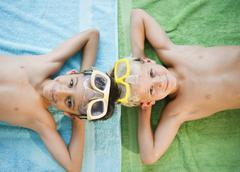 Boys laying on towels wearing swim goggles - stock photo