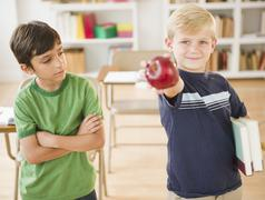 Boy in classroom holding out apple Stock Photos
