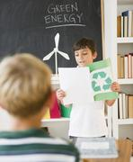 Hispanic boy reading recycling report in classroom Stock Photos