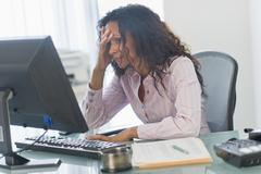 Frustrated Hispanic businesswoman using computer at desk Stock Photos