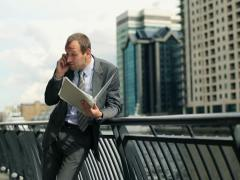 Angry businessman with cellphone and documents in the city NTSC Stock Footage