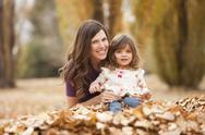 Stock Photo of Caucasian mother and daughter playing in autumn leaves