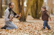 Stock Photo of Caucasian father and son playing in autumn leaves