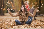 Stock Photo of Caucasian woman playing in autumn leaves