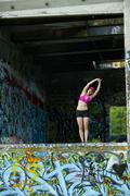 Caucasian woman stretching in abandoned loading dock Stock Photos