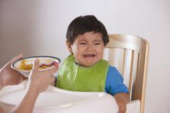 Latinalaisamerikkalainen äiti yrittää ruokkia itku poikavauva Kuvituskuvat