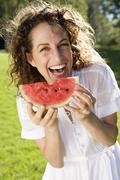 Smiling woman eating watermelon Stock Photos