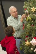 Hispanic boy watching grandfather decorating Christmas tree Stock Photos