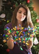 Caucasian woman holding tangled Christmas lights Stock Photos