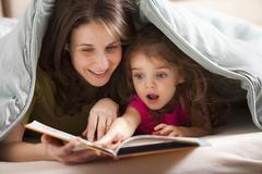 Stock Photo of Caucasian mother and daughter reading book under covers
