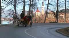 A horsecart passes an ancient Eastern European scene at Lake Bled, Slovenia. Stock Footage