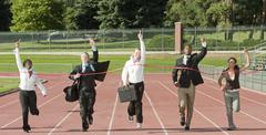 Business people running across track finish line Stock Photos