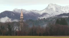 A church is pictured against the Alps of Slovenia, Austria, Switzerland or an - stock footage