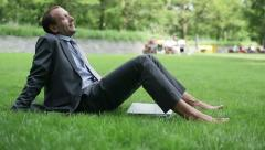Businessman having a break and relaxing in the park HD Stock Footage