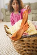 Mixed race girl putting sock into laundry basket Stock Photos