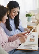 Japanese mother and daughter looking at photo album - stock photo