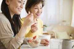 Japanese mother and daughter having breakfast together - stock photo