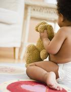 Black baby girl holding teddy bear Stock Photos
