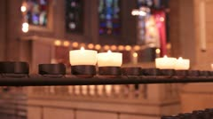 Candles burning against stone glass in church (HD) c Stock Footage