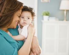 Mixed race mother snuggling baby Stock Photos