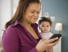 Sekarotuinen äiti tilalla vauva ja tekstiviestit matkapuhelin Kuvituskuvat