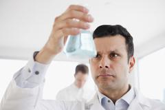 Mixed race scientist holding beaker of liquid Stock Photos