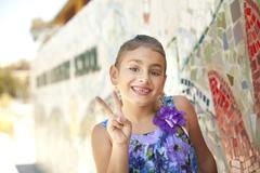 Mixed race girl making the peace sign Stock Photos