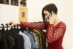 Hispanic woman talking on cell phone in clothing store Stock Photos