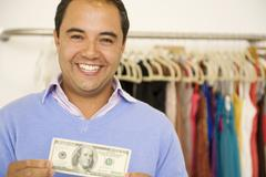 Hispanic man holding cash in clothing store Stock Photos