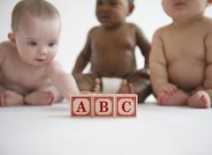 Babies sitting with alphabet blocks Stock Photos