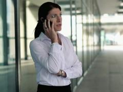 Young businesswoman talking on cellphone in the city NTSC Stock Footage