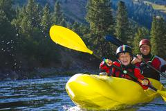 Caucasian father and son kayaking on river Stock Photos