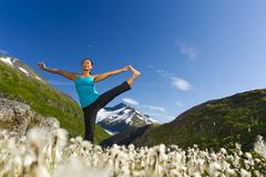 Korean woman practicing yoga with mountain in background Stock Photos