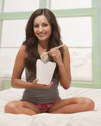 Mixed race woman eating Chinese food from carton Stock Photos