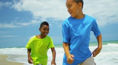 Young African American brothers playing together on beach  Stock Footage