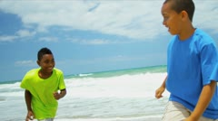 Two diverse boys playing and laughing together on beach   Stock Footage