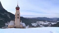 An Eastern church in a snowbound Tyrolean village in the Alps in Austria, - stock footage