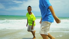 Ethnic happy friends playing together on beach   - stock footage