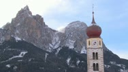 Stock Video Footage of An Eastern church in a snowbound Tyrolean village in the Alps in Austria,