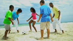 African American family spending summer kicking soccer ball on beach   Stock Footage