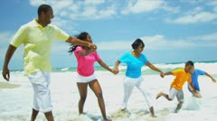 Summer vacation of ethnic family splashing in ocean surfs   Stock Footage
