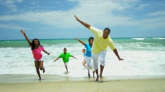 African American family laughing and running together in surfs   Stock Footage